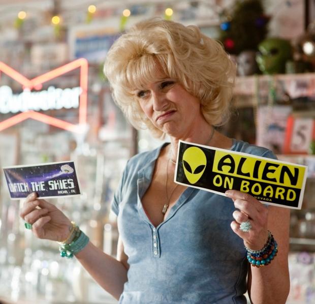 Ägaren till butiken i Area 51 (Jane Lynch) erbjuder klistermärken till nördar