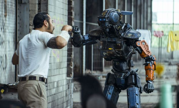 Jose Pablo Cantillo and Sharlto Copley as CHAPPIE in Columbia Pictures' action-adventure CHAPPIE.